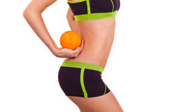 Slim figure of girl in a sportwear with orange in a hand. Isolated on a white background Royalty Free Stock Photography