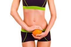 Slim figurerar av flicka med apelsinen i a räcker Arkivbild
