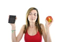 Slim Fit 40s Woman With Apple And Chocolate In Hands To Choose Stock Photo
