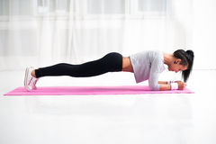 Slim fit girl doing planking core muscles exercise. Indoors at home in the living room side view fitness healthy lifestyle and diet concept royalty free stock photo