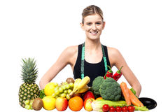 Slim fit girl with fresh fruits and vegetables Royalty Free Stock Photo