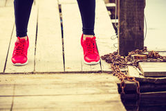 Slim fit legs wearing red sport shoes on wooden pier Stock Images