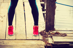 Slim fit legs wearing red sport shoes on wooden pier Stock Photos