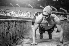 Slim fit man doing outdoor push ups Stock Images