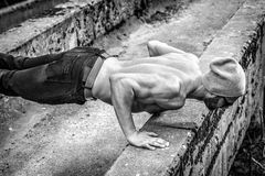 Slim fit man doing outdoor push ups Stock Image