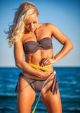 Slim fit woman in bikini with measure tape Stock Photo