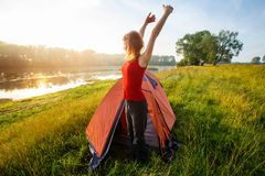 Slim and fit woman hiker. Wakes up and stretches near the tent set on a coast of a river royalty free stock photos