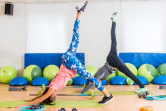 Slim fit women practicing yoga indoors in fitness studio. Two athletic females standing in One-Legged Downward Facing Stock Photography