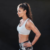 Slim and fit young woman in sportswear. Side view of a slim and fit young woman in sportswear standing with her hands on hips and looking away. Muscular female stock photo