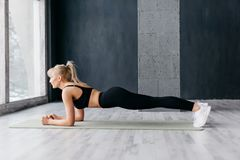 Athletic woman doing plank exercise in white sunny gum stock photos