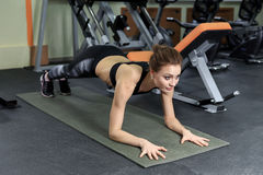Slim fitnes young girl with ponytail doing planking exercise in the gym. Stock Image