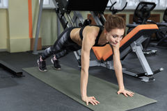 Slim fitnes young girl with ponytail doing planking exercise in the gym. Royalty Free Stock Photography
