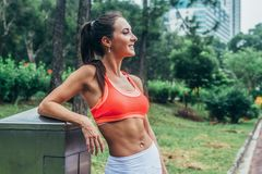 Slim fitness brunette woman with six pack abs wearing pink sport bra standing in city park relaxing after workout stock photos