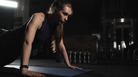Slim fitness girl doing exercise in the gym. Performs push-UPS from the floor. Evening training. Sports lifestyle. Slim fitness girl doing exercise in the gym stock footage