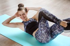 Slim fitness model is exercising on the floor on a green yoga mat Stock Photo