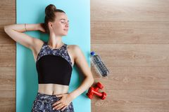 Slim fitness model is exercising on the floor on a green yoga mat Stock Images