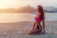 Slim garvade modellen i bikinin som poserar på strandsammanträdesand i ljuset av morgonen på soluppgång med berg och havet in Fotografering för Bildbyråer