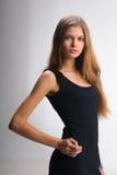 Slim girl in black dress Stock Photos