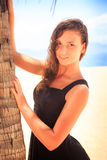 Slim girl in black frock touches palm and smiles Royalty Free Stock Image