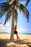 Slim girl in black lace frock barefoot touches palm on beach Stock Photos
