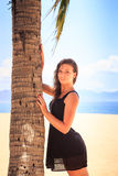 Slim girl in black lace frock barefoot touches palm on beach Royalty Free Stock Images