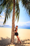Slim girl in black lace frock barefoot touches palm on beach Stock Images