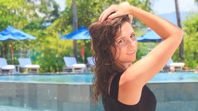 Slim girl in black smoothes hair under palm against pool. European slim girl in short black lace frock closeup smiles and smoothes hair under palm against pool stock video