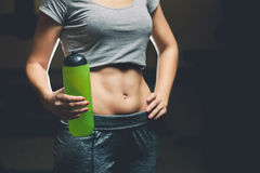 Slim girl bodybuilder, holding a bottle of water while exercising in the gym. Stock Image