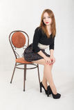 Slim girl on a chair Stock Photos