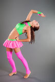 Slim Girl in Dance Costume Poses Bends Body Backward. Beautiful slim brunette girl in fashionable green and pink dance costume stands barefoot bends body Stock Photos