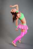 Slim Girl in Dance Costume Poses Bends Body Backward. Beautiful slim brunette girl in fashionable green and pink dance costume stands barefoot bends body Stock Images