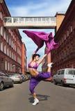 Slim girl dancing with raised leg Stock Photography
