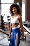 Slim girl with dark curly hair dressed in a sportswear is doing exercises with dumbbells in the modern gym with big royalty free stock image