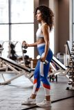 Slim girl with dark curly hair dressed in a sportswear is doing exercises with dumbbells in the modern gym with big stock image