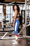 Slim girl with dark curly hair dressed in a sportswear is standing with the heavy dumbbell in her hands in the modern stock image