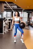 Slim girl with dark curly hair dressed in a sportswear is standing with heavy fitness ball in the modern gym with big stock photos