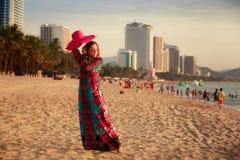 Slim girl demonstrates red hat on beach against city sea. Slim brunette longhaired girl in long colorful dress demonstrates big red hat on beach against city Stock Photo