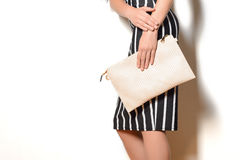 Slim girl in a dress holding beige clutch bag Royalty Free Stock Photos