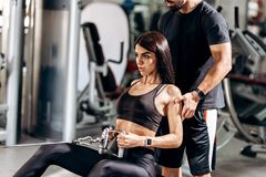 Slim girl dressed in black sport clothes is doing exercises for the abdominals on a special exercise machine under the royalty free stock photography