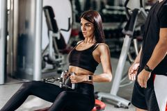 Slim girl dressed in black sport clothes is doing exercises for the abdominals on a special exercise machine under the royalty free stock photo