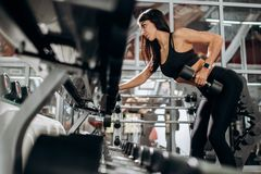 Slim girl dressed in black sport clothes is doing triceps exercise with dumbbell in the gym royalty free stock images
