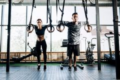 Slim girl dressed black sports clothes and athletic man are doing exercises on gymnastic rings in the gym royalty free stock images
