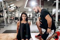 Slim girl dressed in black sports top and tights is doing exercises for the abdominals on the fitness mat in the gym royalty free stock image