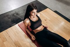 Slim girl dressed in black sports top and tights is doing exercises for the abdominals on the fitness mat in the gym royalty free stock images