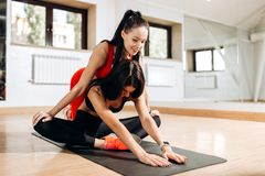 Slim girl dressed in black sports top and tights is doing stretching on the fitness mat with the fitness coach dressed stock image