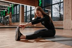 Slim girl dressed in a black sportswear is doing stretching on the fitness mat in the modern gym with wooden decoration stock images