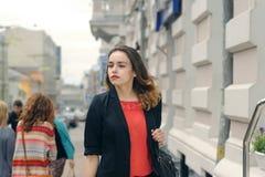 Slim girl goes on city street Royalty Free Stock Image