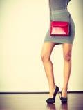 Slim girl in gray skirt with red handbag. Female fashion. Girl wearing gray short skirt black high heels shoes with red leather bag handbag. Studio shot royalty free stock photography