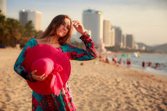 slim girl holds big hat behind back on beach near city sea Stock Images
