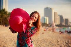 slim girl holds big hat behind back on beach near city sea Royalty Free Stock Photos